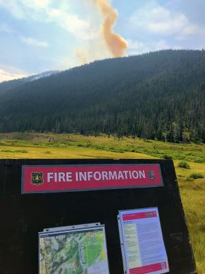 The Bacon Rind Fire can be seen smoldering in the distance beyond one of the information boards along Highway 191.