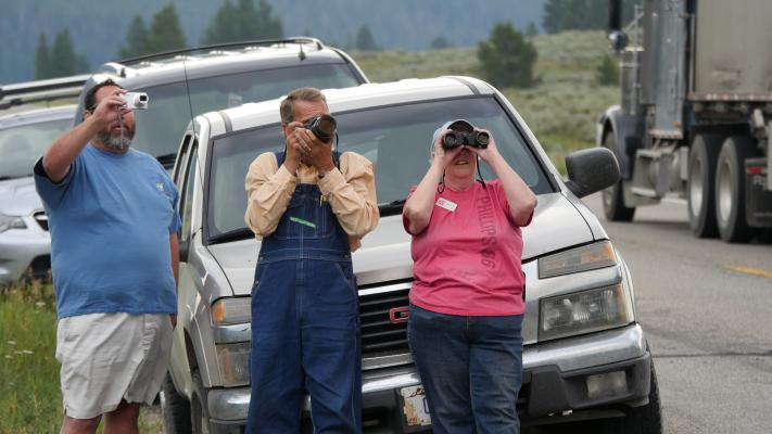 (L to R) Fire watchers Jim Holstein of Big Sky, along with Mike Burdic and Lanette Babylon from West Yellowstone, snap photos of the advancing fire from the side of Highway 191 near the Bacon Rind Trailhead.