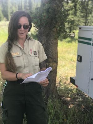 Custer Gallatin National Forest Public Information Officer Lacey England examines a map of the Bacon Rind Fire.