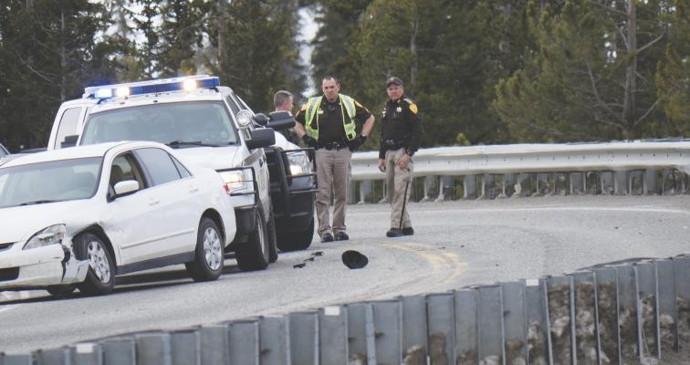 Sergeant Brandon Kelly (center)—who patrols the Gallatin Canyon for the sheriff's office—looks down at a ball cap later taken into evidence. Kelly is flanked by Montana Highway Patrol Sergeant Patrick McCarthy (left) and Gallatin County Sheriff's Deputy Douglas W. Lieurance.