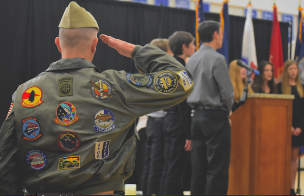 """U.S. Navy Veteran Andrew Jackson salutes during an a capella performance of the """"Star Spangled Banner"""" at the LPHS Veterans Day Assembly held on the afternoon of Nov. 12. Jackson served 24 years of active duty in the military, starting with the Army and moving on to Naval pilot training, flying Lockheed P-3 planes."""