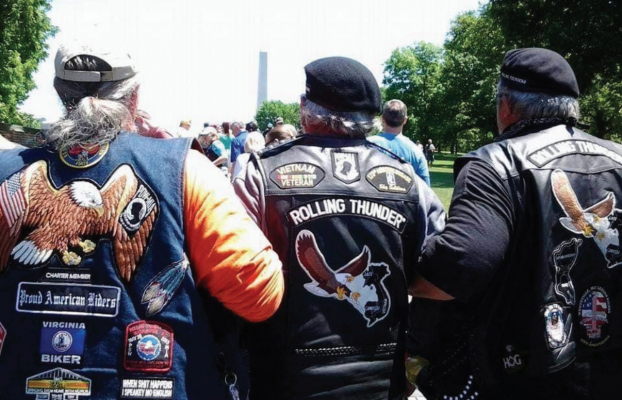 "(L-R) A Rolling Thunder member assists Ronnie ""Crazy Cajun"" Davis to the Vietnam Memorial Wall so he can honor the men from his platoon, then Rolling Thunder Chapter 1, MO. President Terry ""Tiny"" Willey also supports Davis. PHOTO BY JANA BOUNDS"