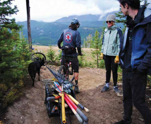 """Patrick Rooney, accompanied by his dog, Juneau, had a trailer of sorts attached to his bike, carrying a variety of tools. Many people on Mountain to Meadow on Sept. 19 had done trail maintenance before, including some Terraflow folks. Rooney encouraged volunteers to ask questions and not go all in with an axe right away. """"A lot of times less can be more, and again it's easy to get overzealous, but ultimately we're going to make the trail better,"""" he said."""