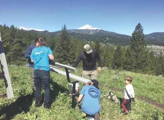 Volunteers install a park bench on Uplands Trail during National Trails Day.