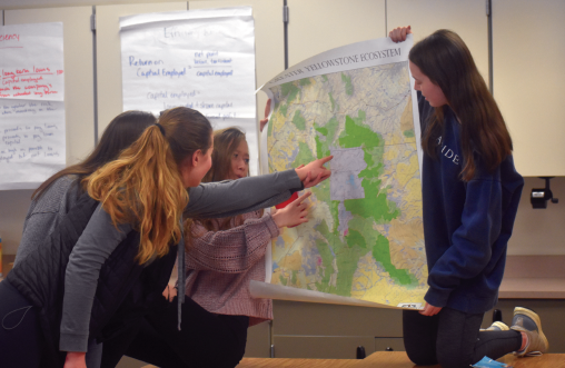 Lone Peak High School juniors Maya Johnsen, Niamh Gale, Noelle Miller, and Livvy Milner look over a map of Yellowstone during an after-school meeting.