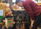 Pat Krause assists Oliver Distad with a word in the book he is reading as Shadow the therapy dog looks on with contentment.  PHOTO BY JANA BOUNDS